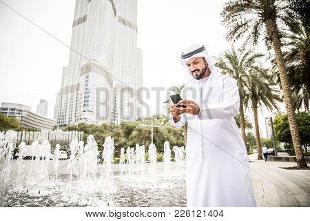 Arabic Businessmen In Dubai Looking At Smartphone