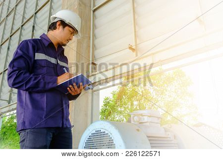 Asian Engineer Or Technician In Blue Collar Safety Uniform And White Security Helmet Checking Motor