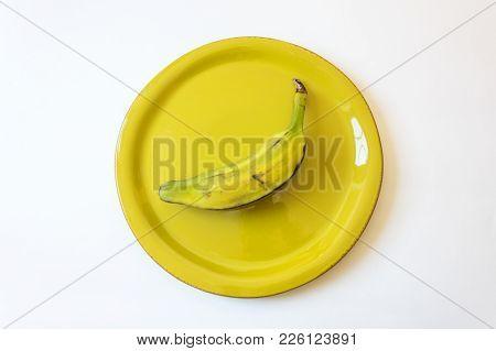 Half Ripe Burro Banana On Bright Green Plate, Also Orinoco, Bluggoe, Horse, Hog Or Largo Banana, Iso