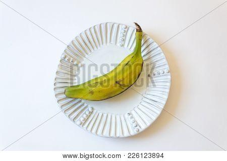 Half Ripe Burro Banana, Also Orinoco, Bluggoe, Horse, Hog Or Largo Banana On White Fluted Plate, Iso