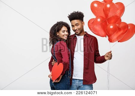 Young Attactive African American Couple Holding Heart Balloon And Paper