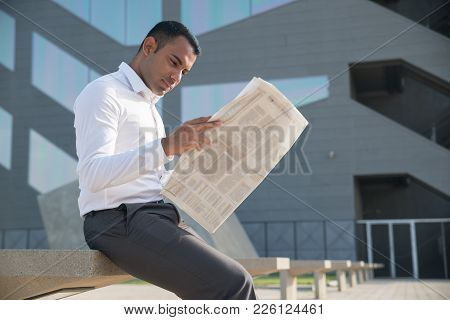 Concentrated Businessman Reading Morning News While Having Break. Serious Confident Young Hispanic A