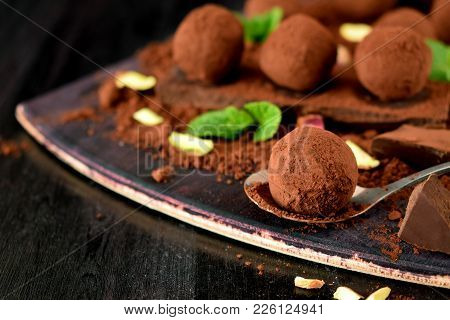 Chocolate Truffles Covered With Cacao Powder, Pistachio Nuts, Chocolate And Mint On A Dark Wooden Bo