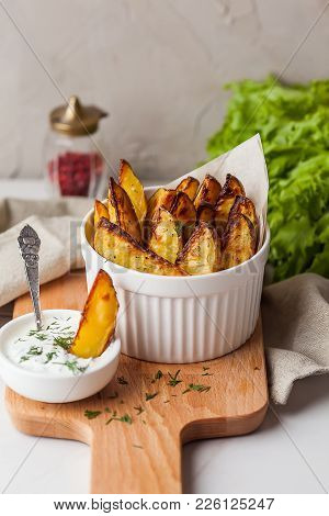 Delicious Roasted Potatoes Garnished With Parsley. Baked Potato Slices With Sour Cream Sauce On Whit