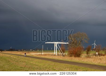 Cyclist Tries To Stay Ahead Of A Heavy Shower On A Bicycle Path In The Dutch Province Friesland