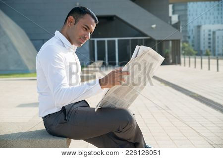 Smiling Young Businessman Interested In News Enjoying Morning Newspaper. Content Latin Male Manager