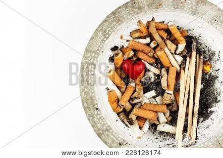 Cigarettes In A Glass Ashtray On A White Background. Treatment Of Lung Cancer. Tobacco Industry