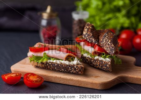 Two Sandwiches With Salad, Fresh Tomatoes And Ham On Wooden Boarde