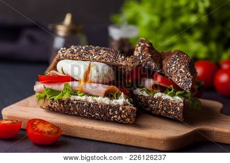 Sandwich With Ham And Poached Egg On Wooden Boarde. Healthy Snack