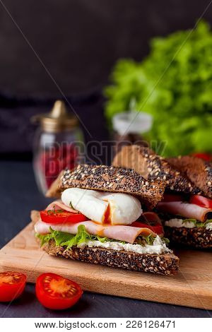 Sandwich With Ham And Poached Egg On Wooden Boarde