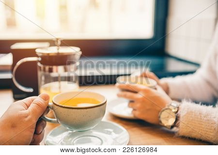 Couple Drink Orange Tea In Cafe Together In The Evening