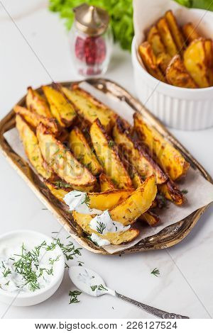 Delicious Roasted Potatoes Garnished With Parsley. Baked Potato Slices With Sour Cream Sauce On A Tr
