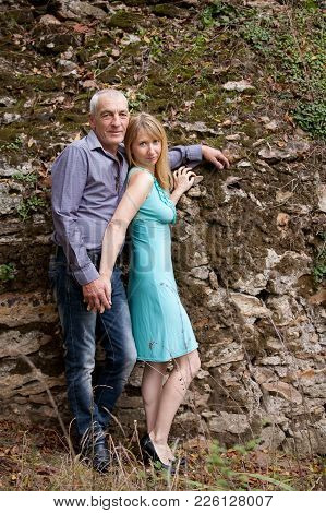 Full Height Portrait Of Happy Couple With Age Difference Standing In The Park On Stones Background D