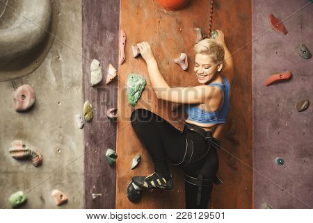 Female Fitness Professional Sport Climber Having Training At Bouldering Gym. Young Happy Woman Smili