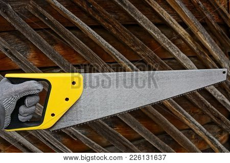 A Hand In A Glove Holds A Hacksaw With A Yellow Handle Against A Wooden Wall Background