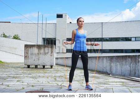 Young, Fit And Sporty Girl Jumping With A Skipping Rope. Fitness, Sport, Urban Jogging And Healthy L