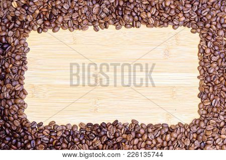 Roasted Coffee Beans Lying On The Wooden Board With Place For Personal Text