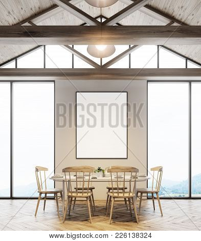 Attic Dining Room Interior With A Wooden Floor, Two Large Windows With A Poster Between Them, And A