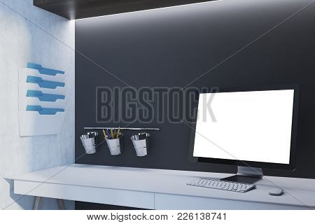 Coputer With A White Screen Is Standing On A White Table In An Office With Black Walls. 3d Rendering