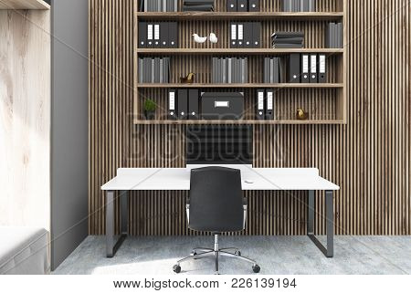 Gray And Wooden Home Office Interior With A Window, A White Desk With A Computer On It And Bookshelv