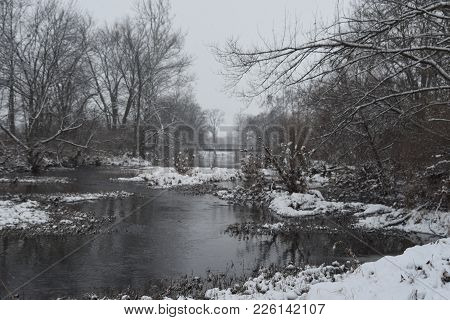 River Creek Stream Running Through A Woods In Winter, Covered With Snow Under A Cloudy Sky With Pede
