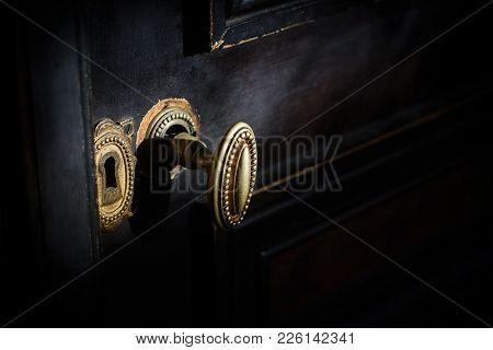 Side View Detail Of Vintage Antique Golden Door Know With Metallic Carvings And Keyhole On Dark Back