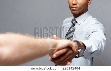 Business Concept - Close-up Of Two Confident Business People Shaking Hands During A Meeting