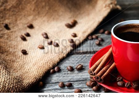 Coffe In Red Mug On Wood Table With Coffee Beans And Cinnamon