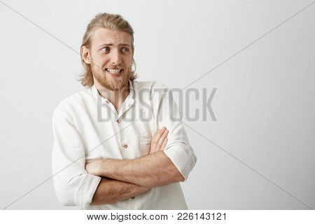 Charming Blond Male With Stylish Haircut Standing With Crossed Hands, Bending Backwards, Expressing