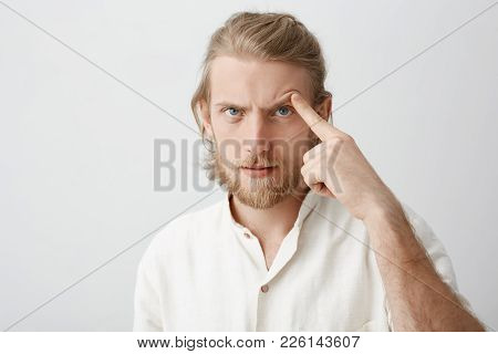 Close-up Portrait Of Serious Attractive Bearded Man With Fair Hair, Lifting Eyebrow With Index Finge