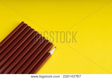 Business Concept - Lot Of Same Pencils And One Different Pencil On Yellow Paper Background. Copy Pas