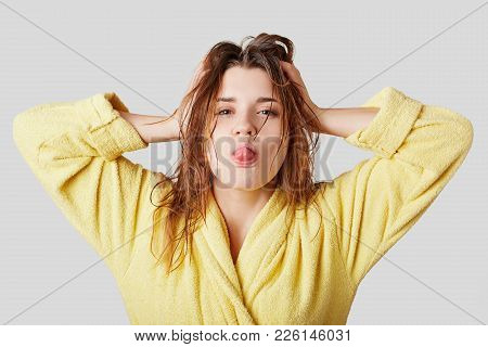 Funny Female Model Makes Grimace, Shows Tongue, Has Wet Hair After Taking Shower, Dressed In Yellow