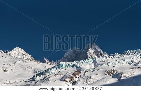 Snow Covered Glacier Du Tour And Aiguille Du Tour On Horizon Against Blue Sky In Afternoon Sunshine