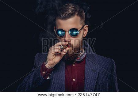 Bearded Guy In Sunglasses Smocking Cigar. Studio Shot