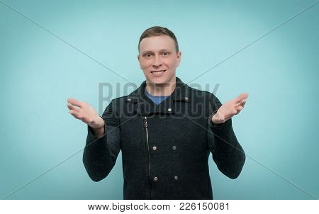 Friendly Smiling Man Waving His Hand And Welcomes Isolated On Blue Background. Glad To See You Have