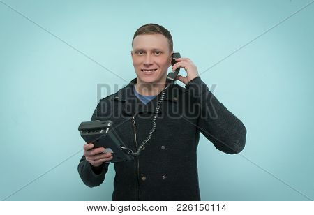 Cheerful Man Is Holding In His Hands A Phone And Is Talking Isolated On Blue Background. Contact Us.