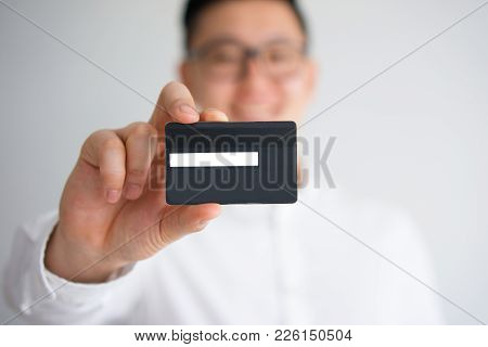 Closeup Of Human Hand Holding Credit Card With Asian Man Out Of Focus In Background. Banker Advertis