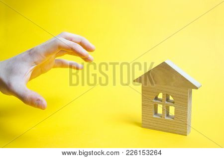 The Hand Is Trying To Seize The House Property Real Estate. Threat, Optimism, High Risk. The Bank Wa