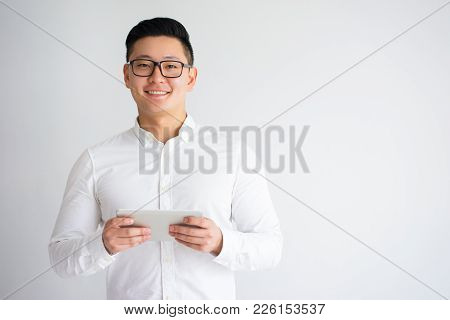 Happy Young Asian Man Wearing Glasses Using Tablet, Surfing Internet. Freelancer Enjoying Work From