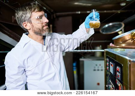 Serious Confident Ingenious Beer Engineer In Protective Eyewear Picking Up Flask With Beer To Check