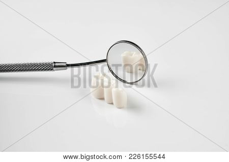 Removed Dental Teeth And Dentistry Instruments For Tooth Removal, Dental Mirror At The Dentist Offic