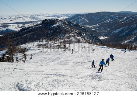 Abzakovo, Russia - March 7, 2005: Skiers Skiing Downhill In High Mountains On A Winter Resort