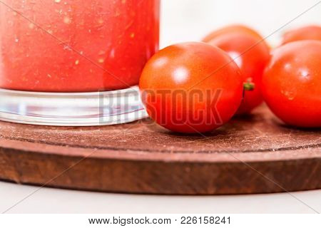 Close Up Glass Bottle Of Tomato Juice With Fresh Tomatoes On Wooden Board Used For Cooking Borscht.