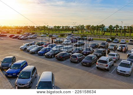 Batumi, Georgia, 2017-12-03: A Lot Of Cars At Open Parking, People Walk, In The Background Of Palm T