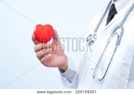 Professional Medical Doctor Holding A Red Heart Ball In The Hospital Background. Concept Of Health C