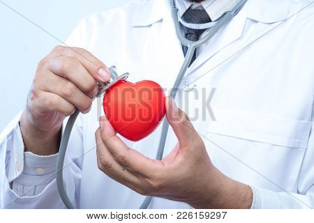 Professional Medical Doctor Holding A Stethoscope Check Up On A Red Heart Ball. Concept Of Health Ca