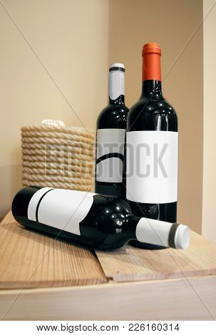 Red wine bottles Three bottles of red wine are standing on wooden crate in the wine cellar Vertical close-up photo template in beige tones