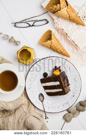 A Piece Of Chocolate Cake On A White Plate With A Cup Of Tea, Glasses And Waffles. Sweet Lunch. Good