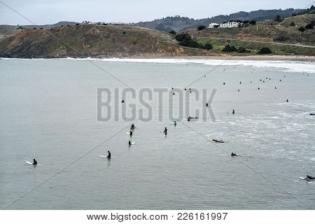 Many Surfers In The Ocean On The Background Of The Beach, Hills And Sky In San Francisco In Californ