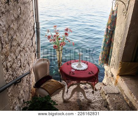 A Beautiful Summer View Of A Sea From A Little Romantic Patio. There Are A Table With A Glass And A
